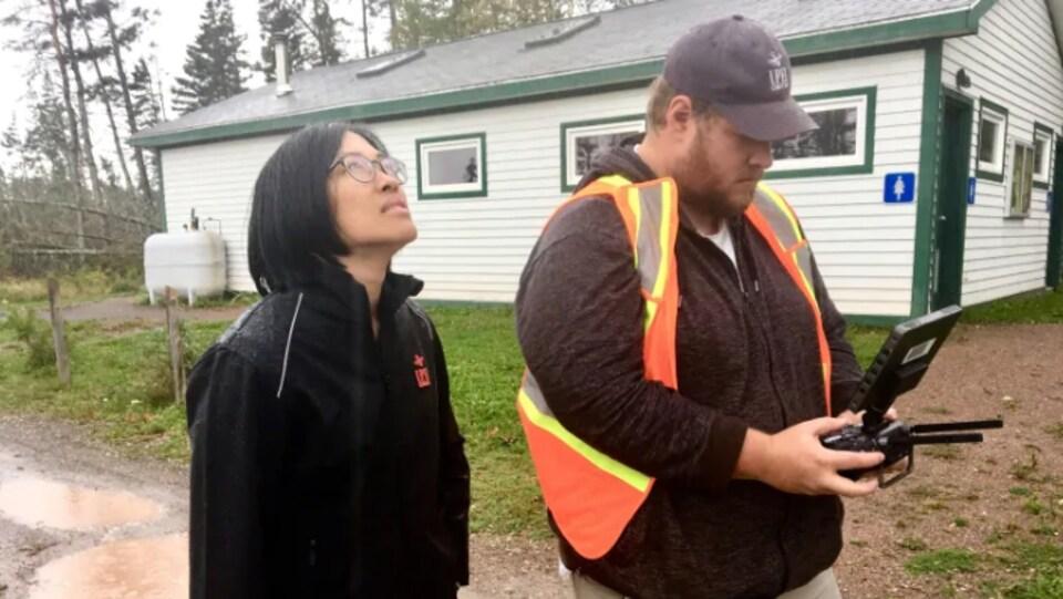 Les deux chercheurs dehors regarde la télécommande du drone qu'ils sont en train d'utiliser.