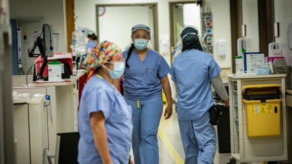 Trois infirmières avec des masques qui marchent dans un hôpital.