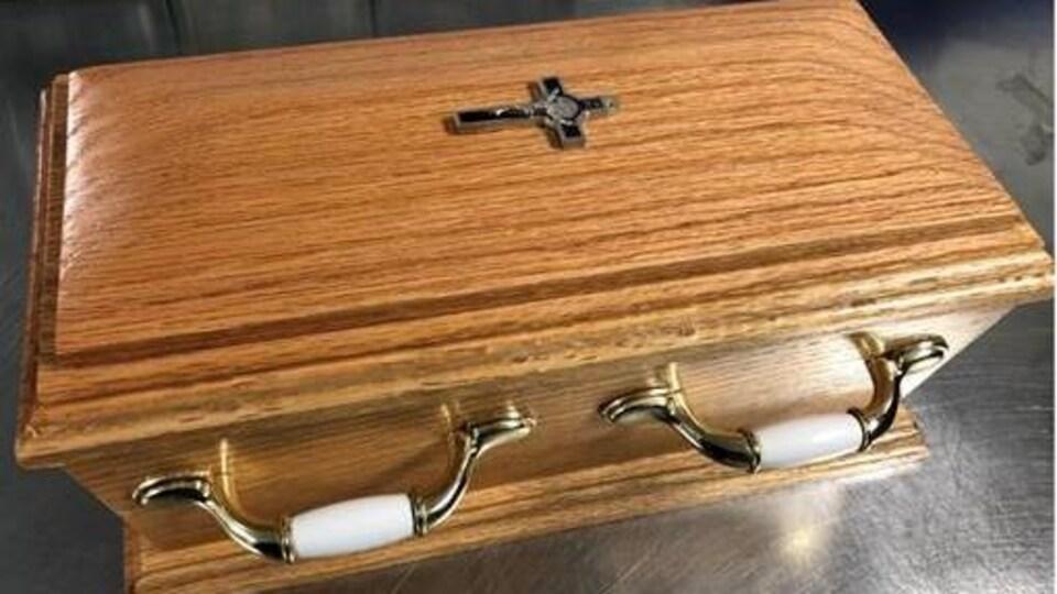 Une urne qui ressemble à un cercueil miniature.