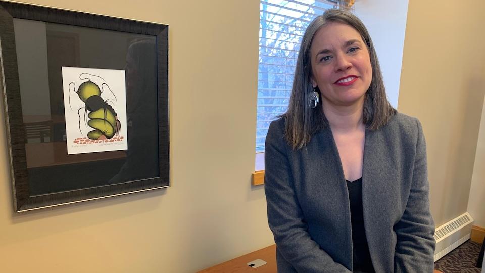 Une femme assise sur une table près d'un tableau accroché au mur.