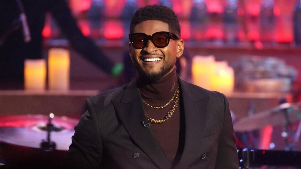 L'homme vêtu d'un veston et d'un col roulé bruns porte des lunettes de soleil et sourit.