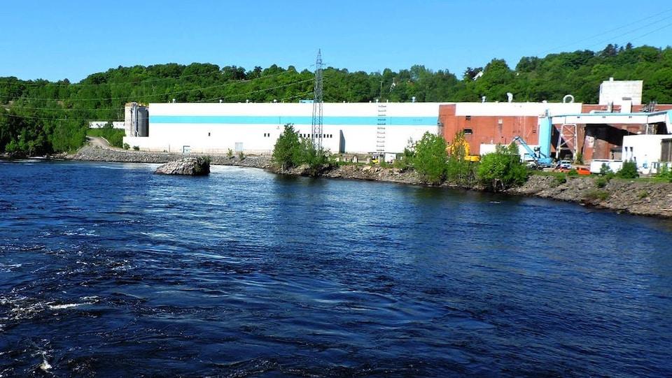 On voit l'usine (un grand bâtiment blanc de forme rectangulaire) au bord de la rivière Saint-Maurice.