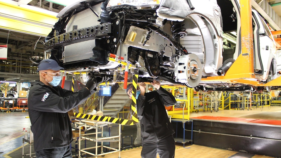 Deux hommes masqués, séparés par un écran en plastique, travaillent sur une voiture dans une usine.