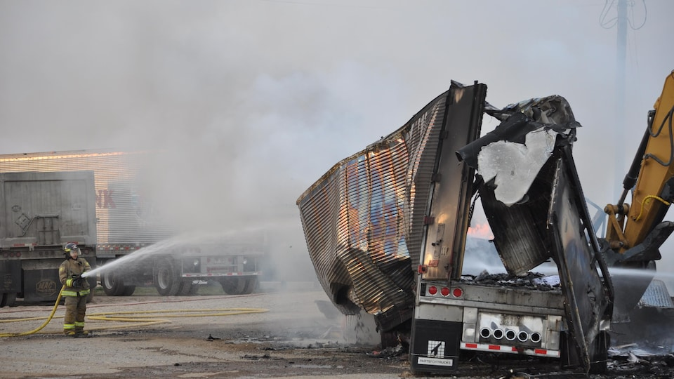 Un pompier arrose des flammes sur la scène de l'incendie.