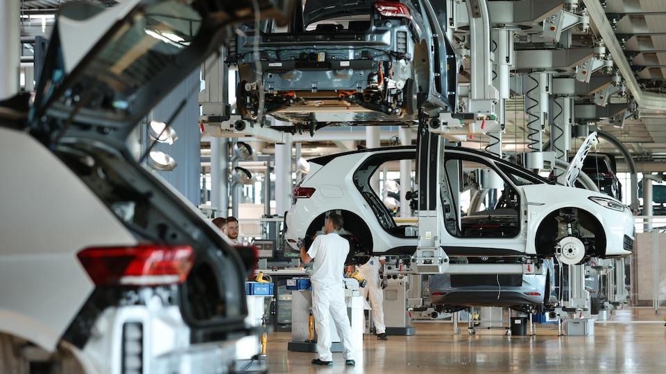 Des ouvriers assemblent des voitures électriques Volkswagen.
