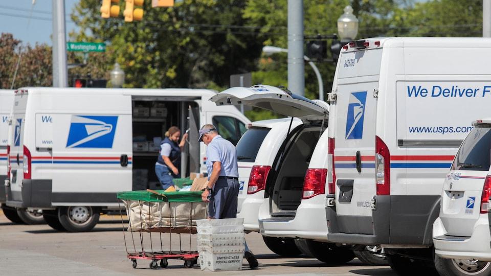 Des employés chargeant du courrier dans des camions de livraison.