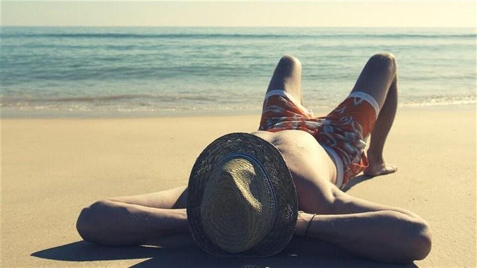 Un homme étendu au bord de l'eau sur le sable d'une plage