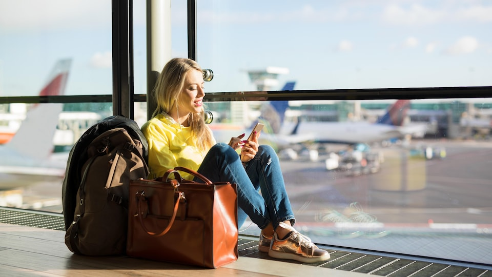 Une femme consulte son téléphone cellulaire en attendant son vol à l'aéroport.