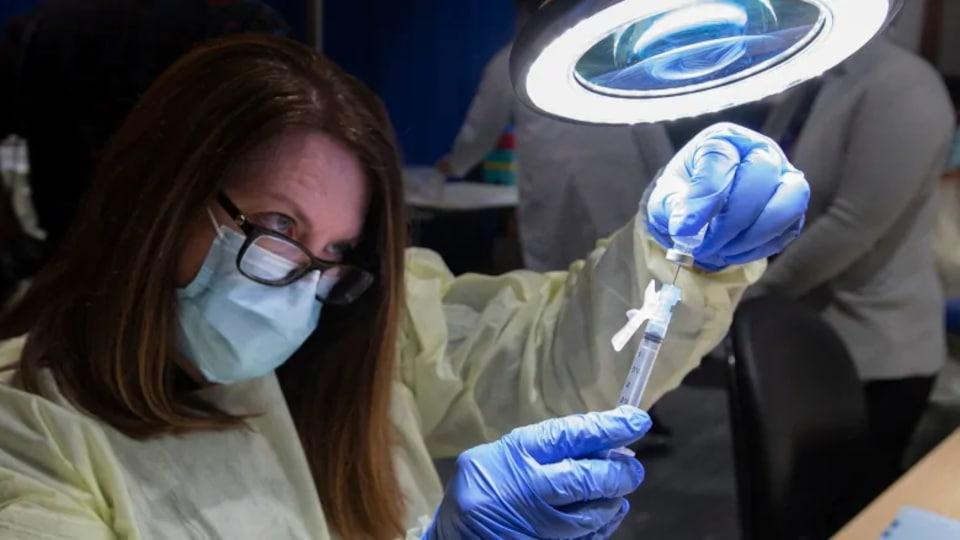 A pharmacy technician prepares an injection.