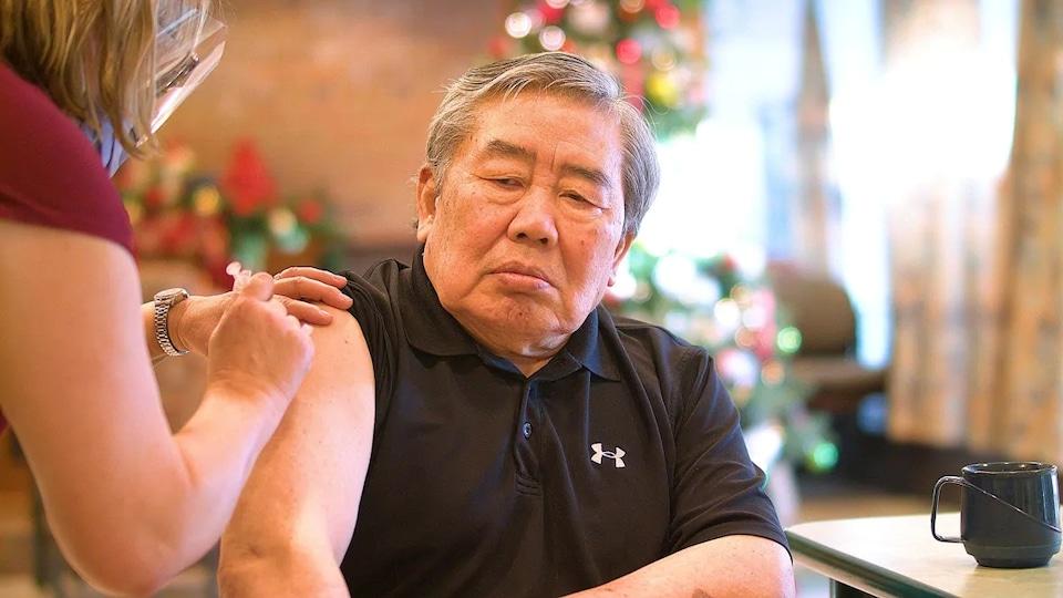 Un homme âgé reçoit un vaccin.