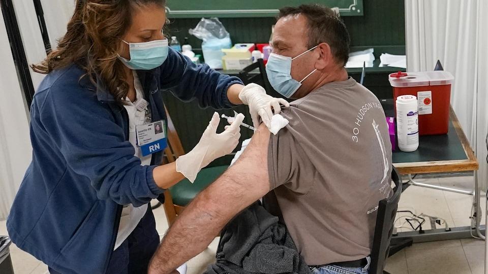 Un métallurgiste se fait vacciner contre la COVID-19 lors d'une clinique de vaccination pour les travailleurs de la construction, le 14 avril 2021 à Elmont, dans l'État de New York.