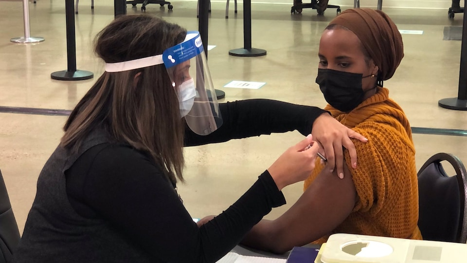 Sahra Kaahiye est assise aux côtés d'une femme qui a une seringue dans la main et qui s'apprête à piquer Sahra.