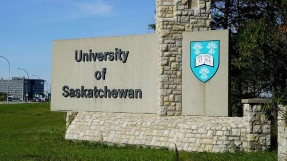Gros plan sur le monument en pierres planté à l'entrée de l'Université de la Saskatchewan sur lequel est inscrit le nom de l'établissement.