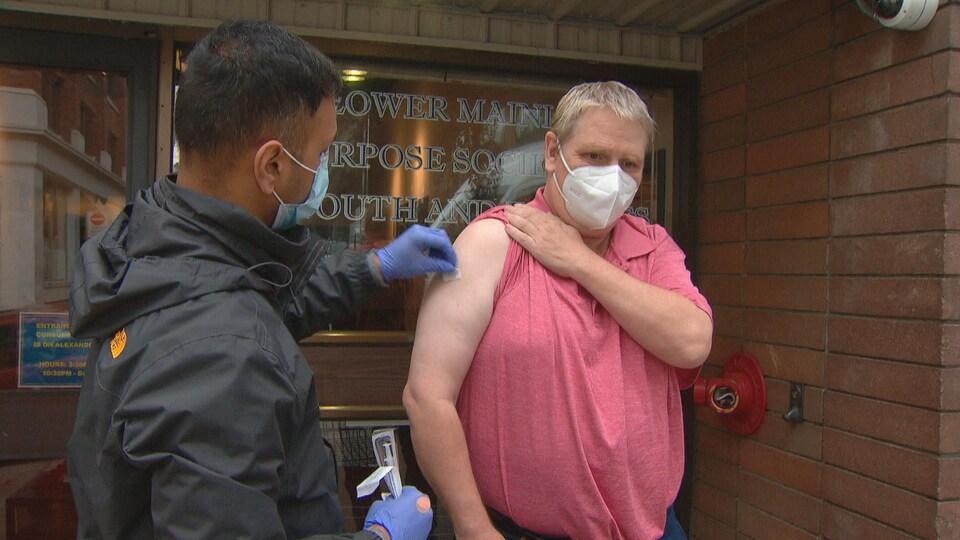 Un homme se prépare à recevoir un vaccin à l'extérieur d'un établissement.