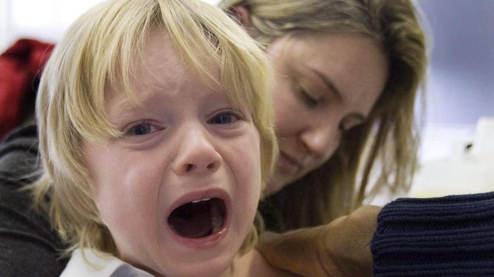 Evan Tordorf, 4 ans à l'époque, pleure après avoir été vacciné, tandis que sa mère, Karen Joly, tente de le consoler.