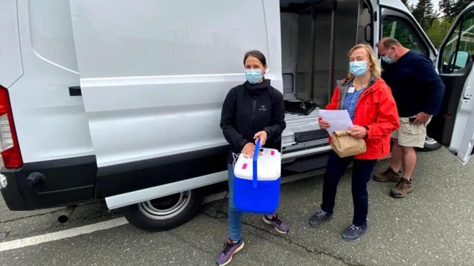 Deux femmes et un homme devant un camion. L'une d'elles transporte une glacière.