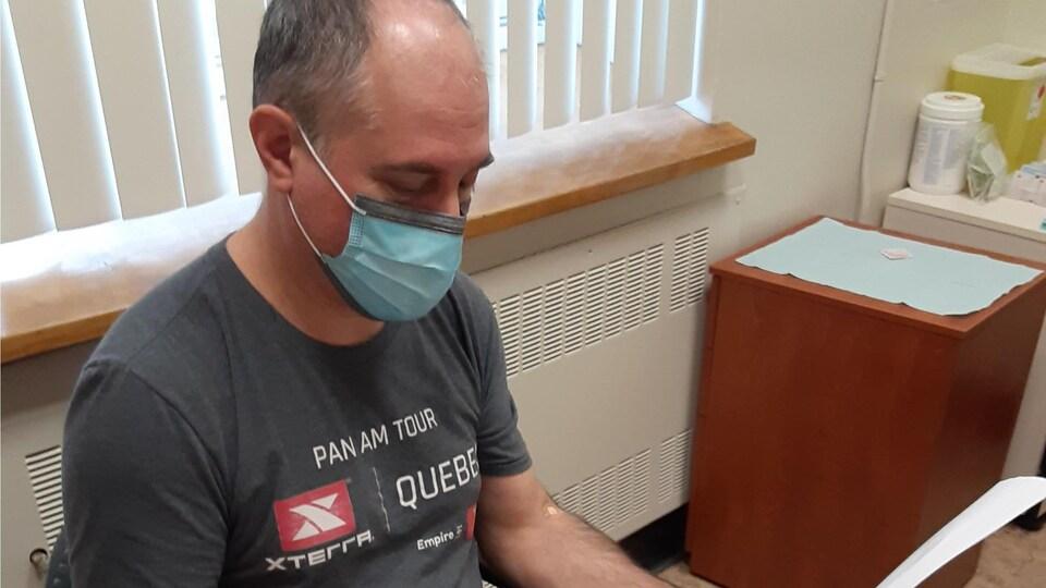 Plan rapproché d'un homme assis dans un bureau de médecin, avec un masque, qui consulte un document.