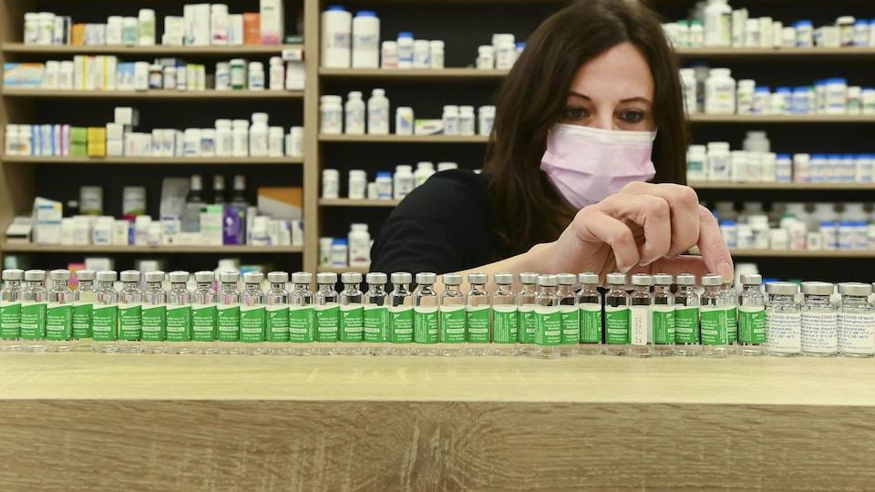 Une pharmacienne range les flacons vides du vaccin anti-COVID-19 d'AstraZeneca-Oxford qu'elle a inoculé à ses clients.