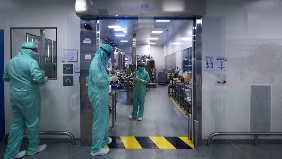 Des techniciens de laboratoire en combinaison de protection dans un centre de recherche.