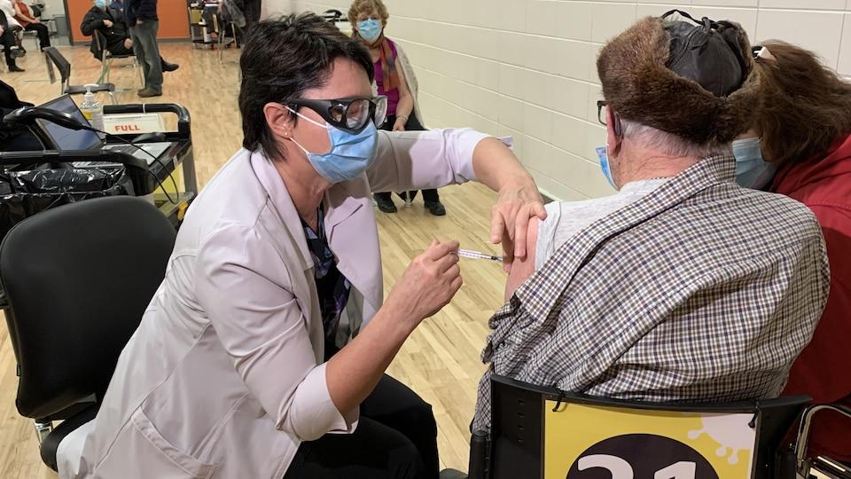 Une infirmière administre une dose à un homme de dos.