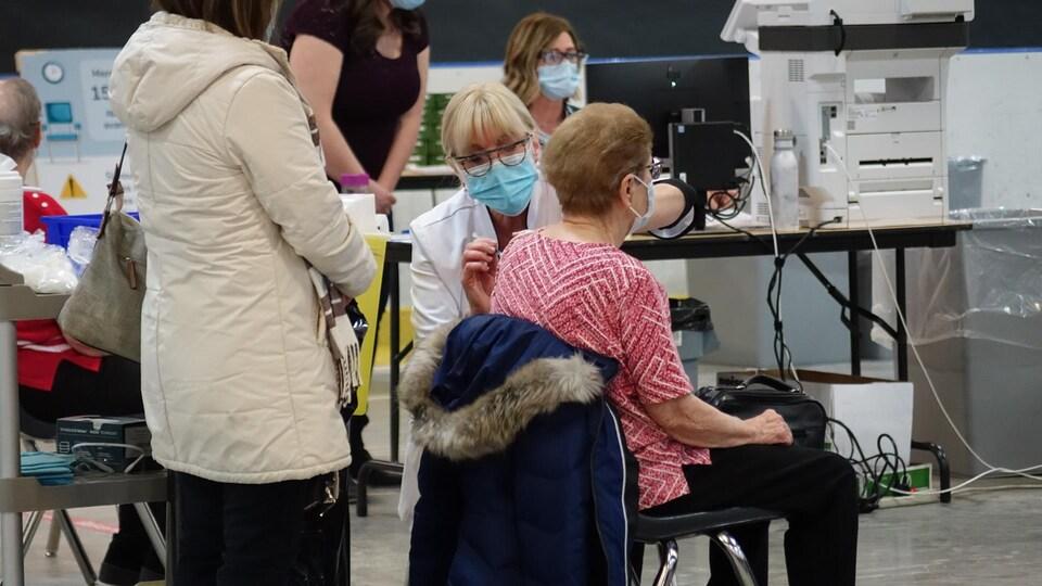 Une femme reçoit une dose de vaccin contre la COVID-19, le 11 mars 2021 à Matane.