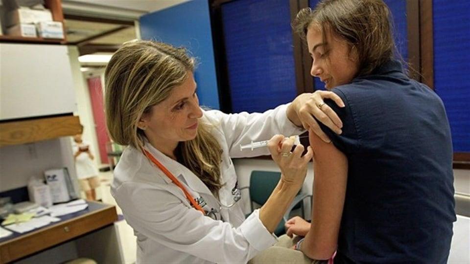 Une infirmière vaccine une jeune fille dans le bras.