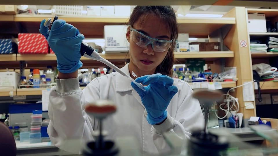 Une chercheuse tient une seringue dans ses mains.