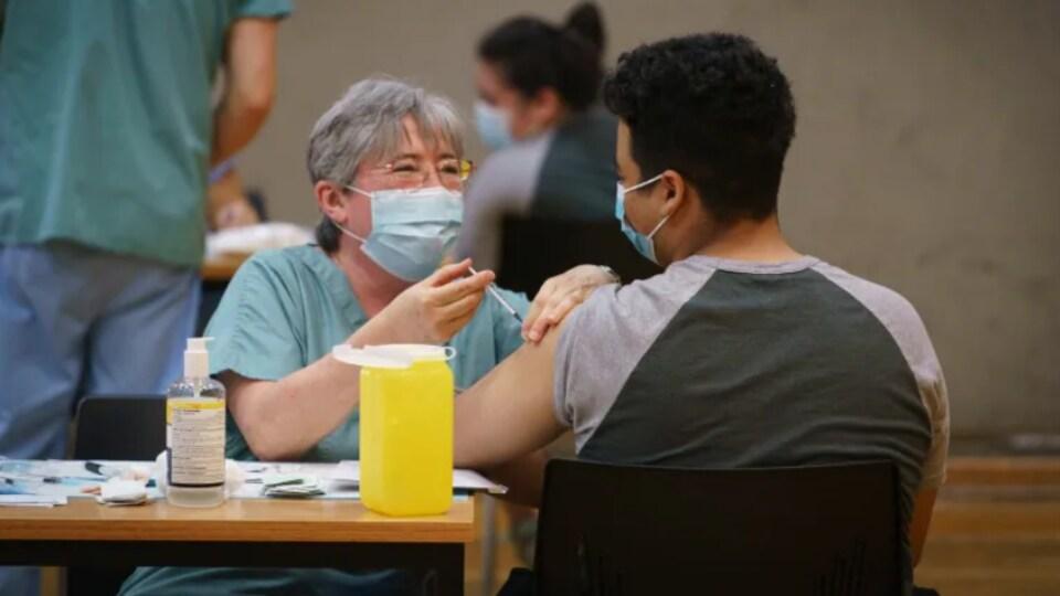 Une professionnelle de la santé injecte un vaccin à un étudiant.