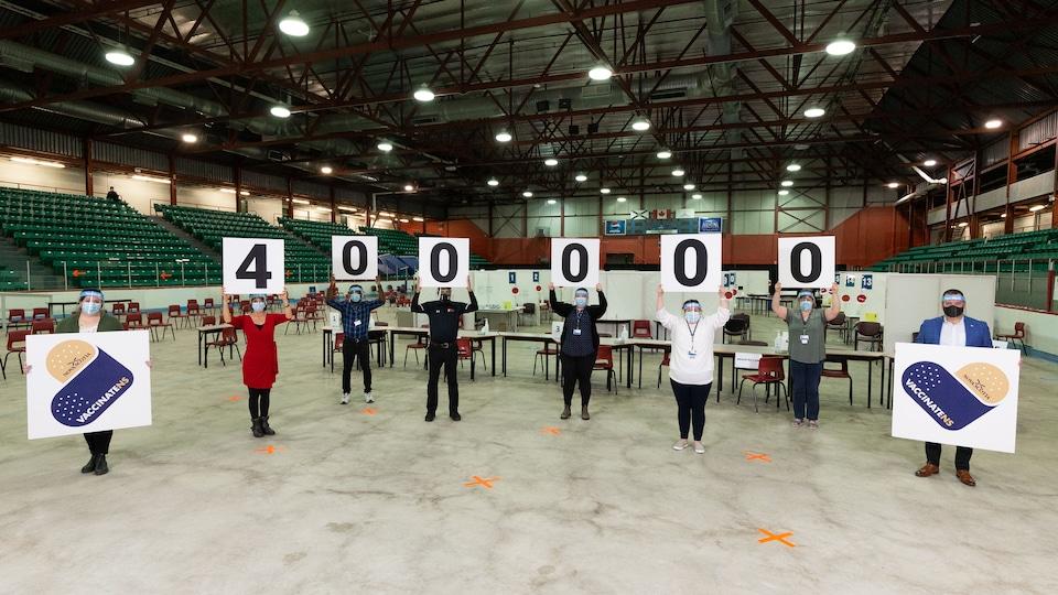 Des infirmières tiennent des affiches qui ensemble forment le chiffre 400 000.
