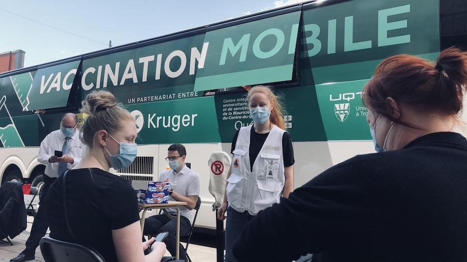 Deux personnes vaccinées attendent dans l'aire d'attente après avoir reçu leur vaccin.