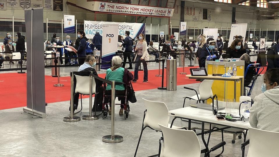 À l'intérieur de l'aréna, des gens sont triés pour se faire vacciner.