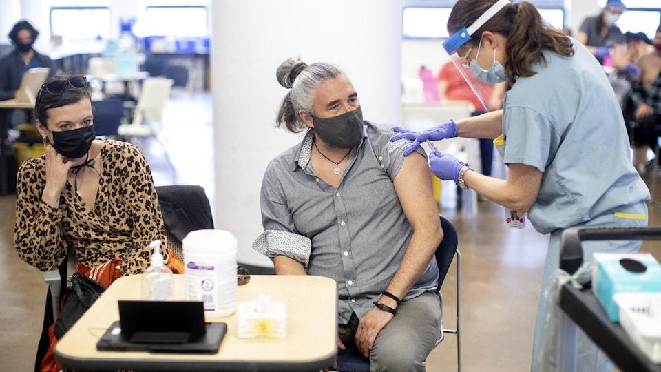 Un homme assis se fait vacciner par une infirmière. Une femme est assise à côté de lui.
