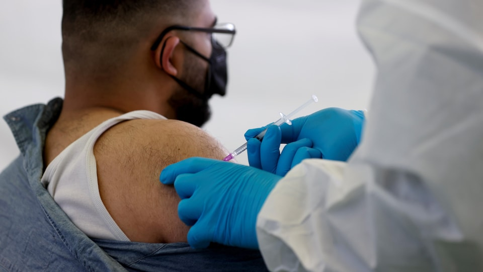 Un homme de dos qui se fait vacciner.