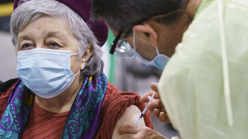 Une femme se fait vacciner sur le bras gauche.