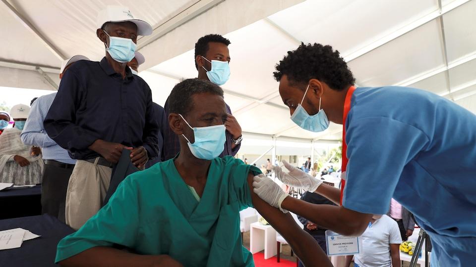 Des gens attendent derrière l'homme en train de se faire vacciner.