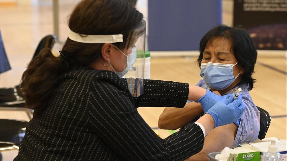 Une dame assise sur une chaise en train de se faire vaccinée par une autre dame.