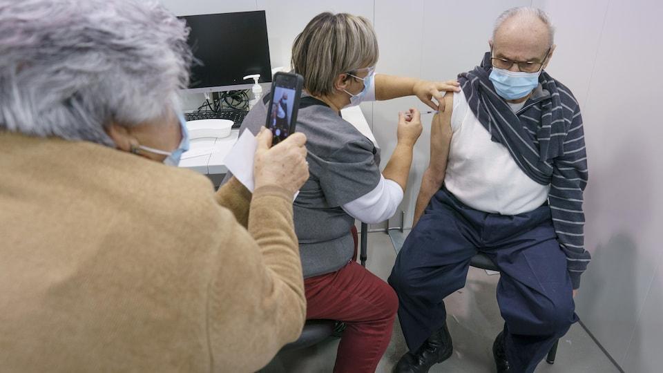 L'homme est assis sur une chaise et se fait vacciner. Sa femme prend une photo avec son cellulaire.