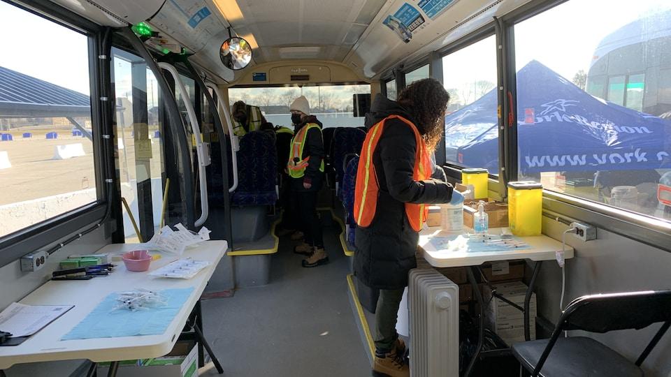 Des personnes dans un autobus aménagé avec des tables de travail.