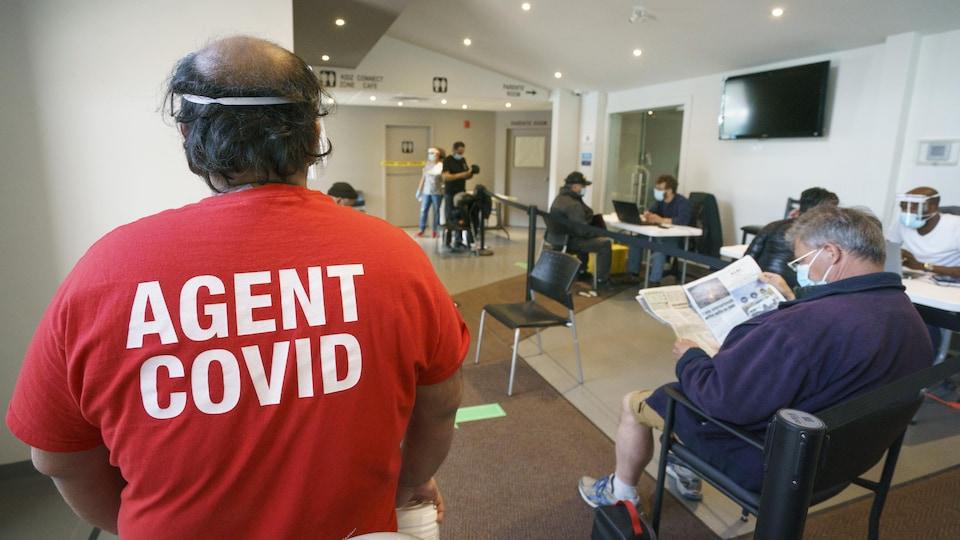 Un homme de dos avec un t-shirt sur lequel on peut lire : «Agent COVID».