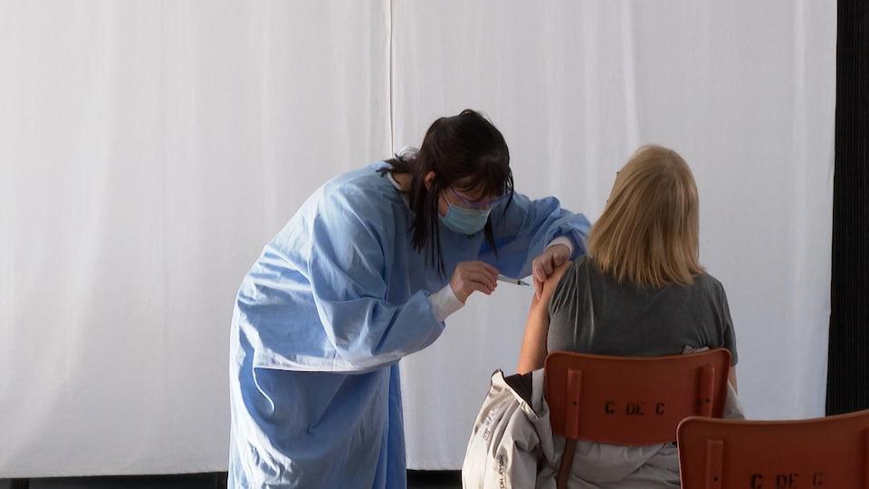 Une infirmière vaccine une femme dans le Nord-du-Québec.