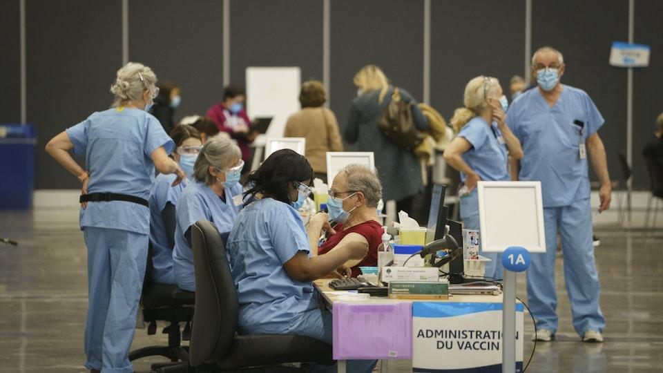 De nombreux travailleurs de la santé portant des vêtements bleus et des masques sont à pied d'œuvre dans une salle du Palais des congrès
