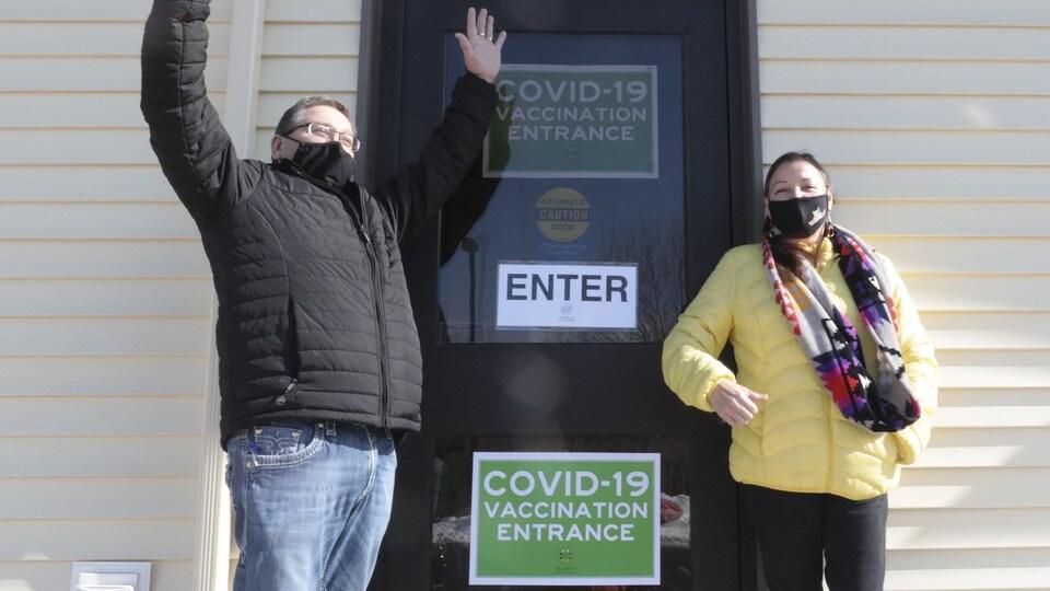 Bob Gloade lève les deux bras et Patsy Paul-Martin se tient debout près de la porte d'entrée du centre de vaccination.