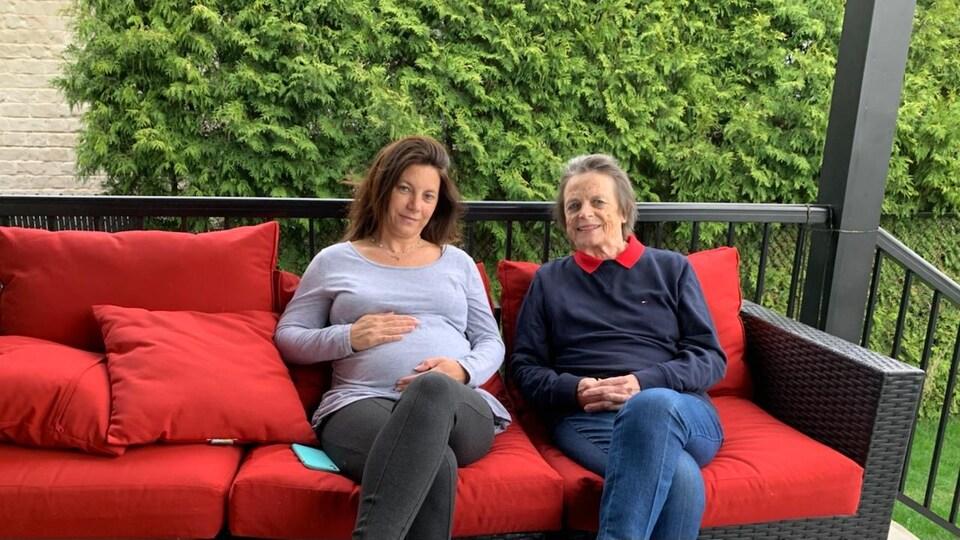 Une femme enceinte est assise aux côtés de sa mère sur un sofa sur une terrasse.