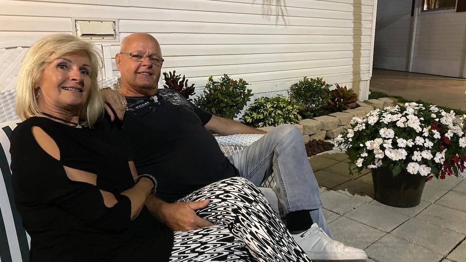 Un couple assis devant leur demeure en Floride.