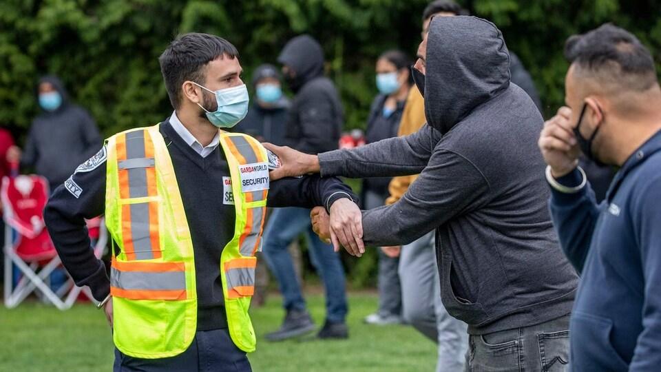 Un homme attrape le bras d'un garde de sécurité dans un parc où l'on voit des gens faire la queue.