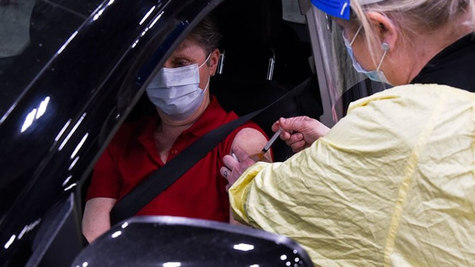 Une infirmière injecte une dose de vaccin à une personne assise dans sa voiture.