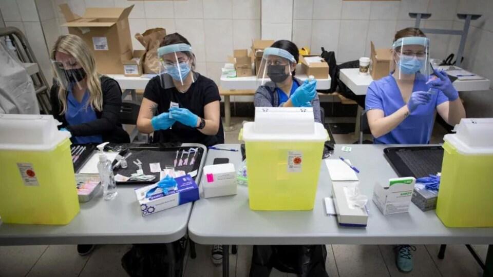 Une table avec quatre infirmières préparant des vaccins contre le coronavirus.