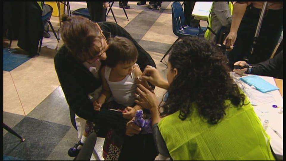 Des Manitobains se font vacciner contre la grippe H1N1 dans une des cliniques d'urgence de Winnipeg en 2009.
