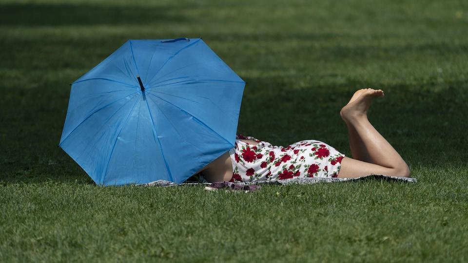 Une femme allongée dans un parc se protège du soleil sous son parasol.