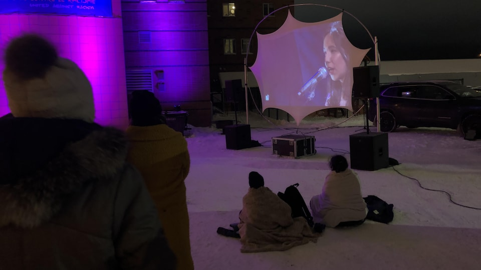 Une jeune femme chante au micro. Son image est projetée dans un stationnement et des personnes présentes la regardent.